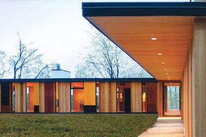 In an effect inspired by the forest that surrounds it, views through this new lakeside home shift with one's perspective. Its unfinished red cedar siding will gray to blend with the tree trunks.