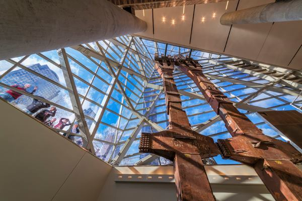 Visible through the entry pavilion's glass atrium, two columns from the north façade  of the World Trade Center reach upward from the Memorial Museum's bedrock floor.