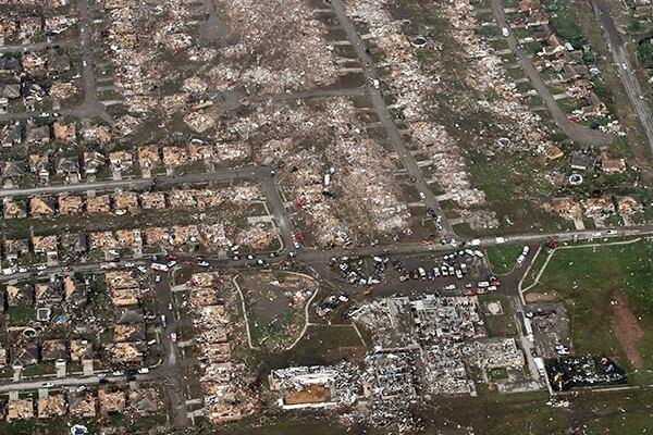 This aerial photo shows the remains of homes hit by a massive tornado in Moore, Okla., on Monday, May 20, 2013. A tornado roared through the Oklahoma City suburbs Monday, flattening entire neighborhoods, setting buildings on fire and landing a direct blow on an elementary school. (AP Photo/Steve Gooch)