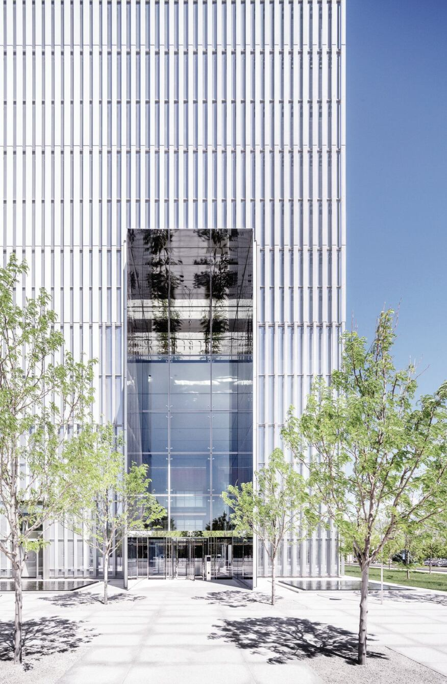 The public entrance at the southwest corner of the site is framed by projecting panels of polished stainless steel. Phifer used this treatment on all of the major openings in the building's aluminum veil.