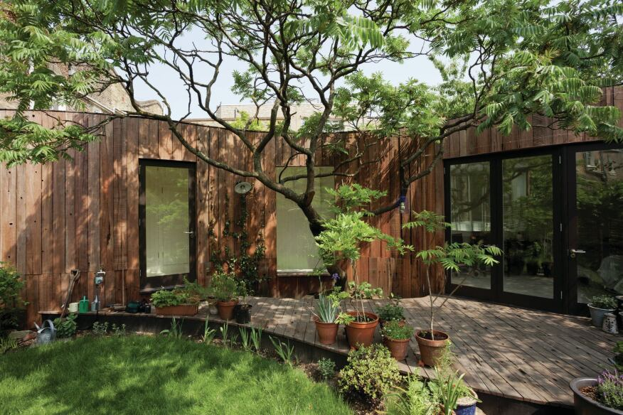 Large windows overlook the deck built around the sumac tree and allow natural light to flood the interior.