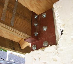 One of the most sensitive locations for hurricane and tornado resistance is the junction between walls and roof. Shown here, roof joists are secured with two steel straps to headers, which are solidly attached to the concrete walls.