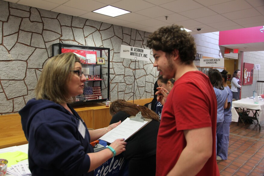 Ann Sweck, an HR representative from Whiteley Plumbing and Heating, in West Chatham, Mass., interviews a student at a job fair at Cape Cod Technical High School. Sweck said that students come to work for the summers and end up staying with the company long term.