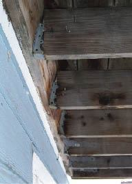 Figure 3. The rotating ledger in this photo was a complete surprise to the homeowner. This ledger has completely pushed the joists out of the hangers, and the deck is at risk of collapse. Ledgers that slowly pull away often rotate from the top, making the hazard less noticeable from beneath.