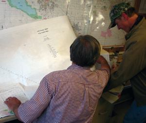 Paper, begone! Larvaciding field supervisor Rod Hale (left) no longer sorts  through hundreds of maps to develop application schedules or determine  treatment efficacy. Instead, he queries a database that's updated daily with  information gathered by field crew members, like Tony Parent, who tap in  data on a touchscreen PDA. Photo: Ada County Mosquito Abatement District