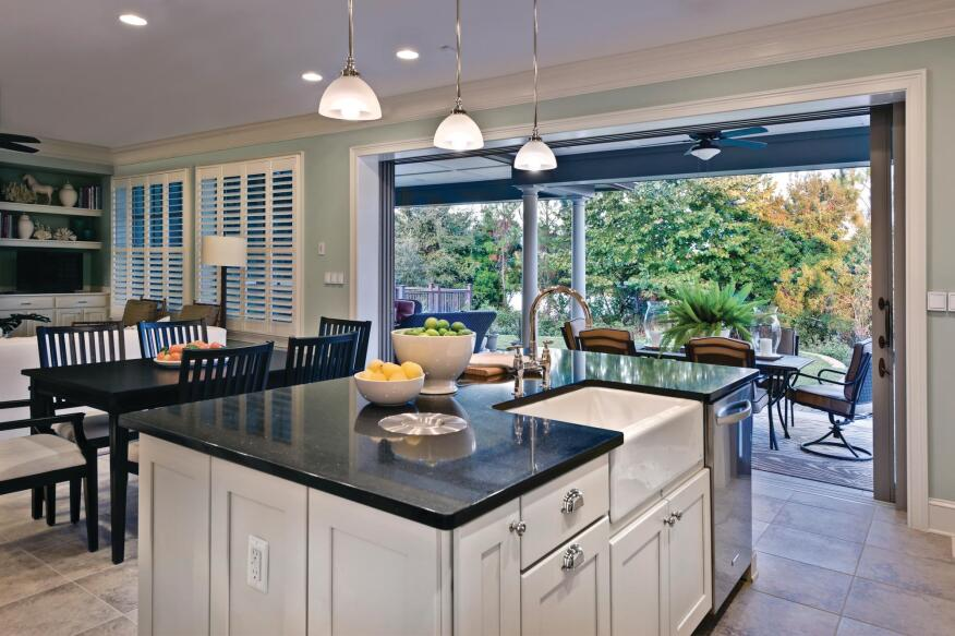 """Big Island An island measuring 7 feet 6 inches by 4 feet 6 inches and topped with a Dupont Zodiaq quartz countertop (seen here in """"licorice"""") provides a versatile surface for organizing, baking, food prep, and clean up. In lieu of a garbage disposal, the countertop includes a recessed, compost bin with a bucket handle for transporting vegetable scraps from kitchen to garden."""