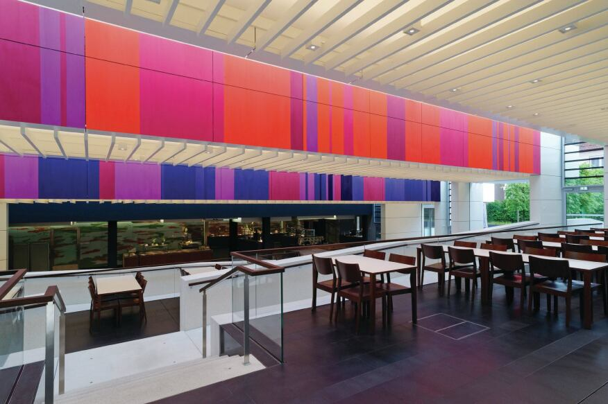 Artwork panels in shades of red, magenta, purple, and blue line the ceiling slab fascia of the three-tiered ceiling and cast additional hues of light into the space.