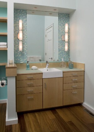 "The homeowners did not need the vanity to be accessible, so remodeler Dan Tibma installed standard-height cabinetry here. He used recessed lights above the vanity, but says, ""Lighting above the sink casts a shadow, so we also like to install lights that flank the mirror."""