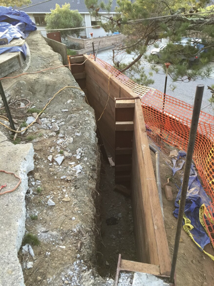 The existing concrete slab flanking the edge of the pool was demolished to expose the steel columns supporting the retaining wall. Blocks held the new 3x12 PT timber laggings in place until the excavation could be backfilled.