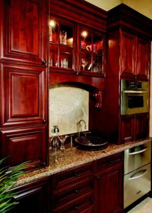 CABINET MEMBERS: The kitchen is outfitted with cabinetry by Canac Kitchens—Virginian maple  Hazelnut with black antiquing for the main storage and Virginian maple  Riverstone with chocolate glazing on the island. Both styles feature full-access  boxes, concealed hinges, and solid wood drawers with dovetail construction.