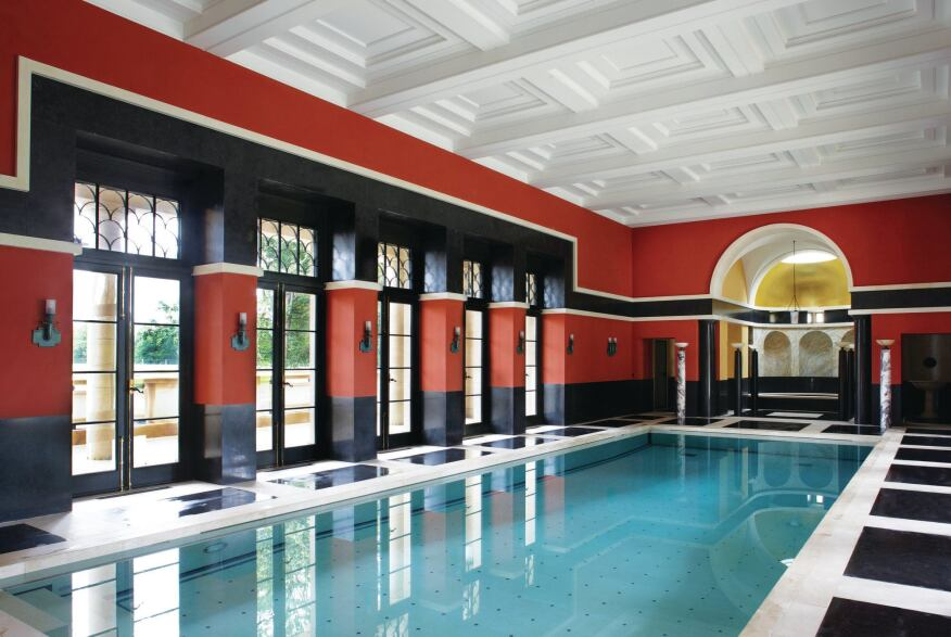 The marble floors continue into the pool hall, which is lined with Pompeian red walls. The hot tub in the apse is flanked by a sauna and a steam room.