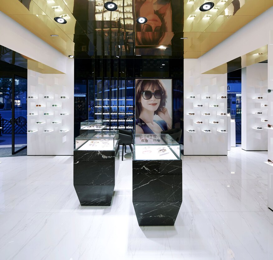 A general view of the store interior. 4000K adjustable LED downlights aim down to the floor, creating an evenly distributed glow on the white marble floors, which is then reflected on the gold ceiling.