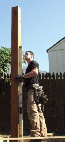 The posts are left long, placed in holes, and plumbed in two directions prior to backfilling.