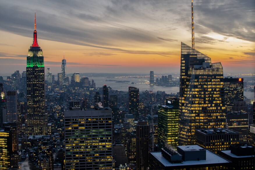 New York City's illuminated skyline at dusk.