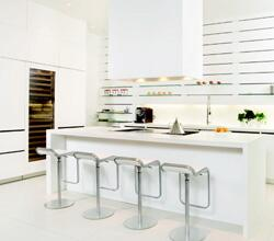 The kitchen includes an eating bar.  Shelves are cleverly created by inserting glass panels into wall slats. The effect maintains the crisp appearance of the space.
