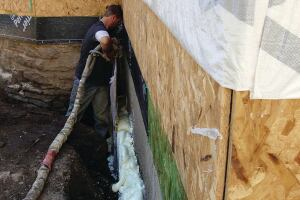 At wide spots in the trench, the foam is poured to a consistent thickness against a sheet of OSB.