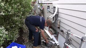 Master plumber Dave Ragsdale purges the refrigerant lines of a 12,000-Btu Fujitsu mini-split heat pump. In tandem, the solar panels and heat pumps will relieve the home's existing oil boiler of much of its annual job.