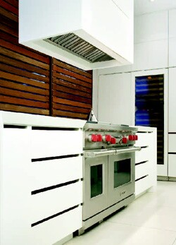 The kitchen, which is open to adjacent living areas, can be concealed behind movable wood-slatted panels.
