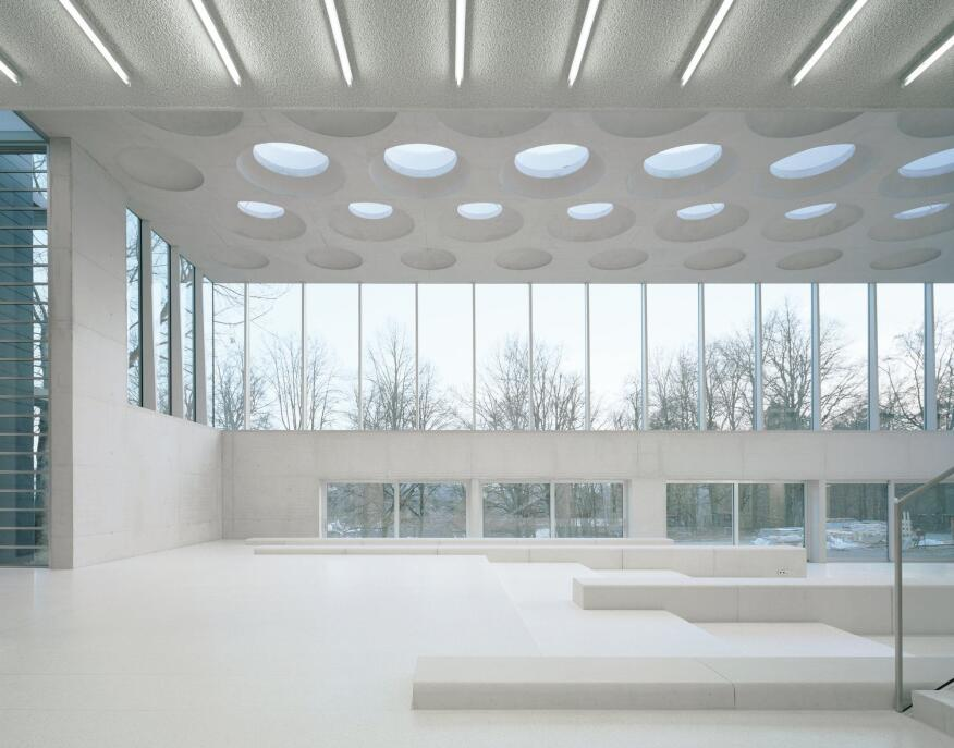 "The entire 25-meter-square concrete ceiling was poured in place in a single session on ""a very cold day"" in the middle of winter, Ecker says. The architects originally considered other materials—wood and metal among them—but eventually Ecker suggested concrete. ""That's kind of the way our office works,"" Piotrowski says. ""I'm constantly involved in the really fine details of what we're doing, and Dea comes and shakes things up and will think about things a little differently."" The walls of the structure are also formed from concrete?its high flyash content gives it the white color?and the floors are terrazzo, so even though the tones are very light, they can take the wear and tear of hundreds of high schoolers. ""We find that if you use true materials, and you leave them exposed, there's not really much that can happen to them that you cannot remove,"" Ecker says. The benches in the main assembly hall are also made from concrete, and were cast with formwork from Max Frank."