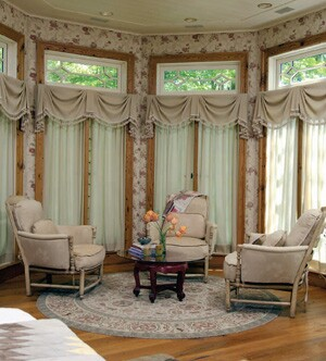 "The nearby seating area (left) provides a cozy place for all the home's inhabitants. ""The seating area in the master bedroom is where the four dogs like to rest,"" builder Jim Gibson says. The area has a fireplace and beadboard ceiling and is ornately decorated with fabric wallcovering and scalloped window treatments."