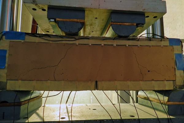 A notched beam undergoes a four-point bending test, which causes its surface to crack.