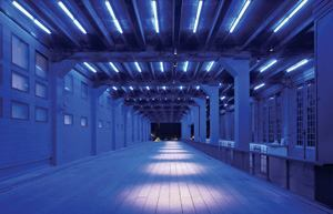 The Chelsea Market tunnel along the High Line in New York. Lighting designer Hervé Descottes uses this portion of the project to discuss how the space assumes a different identity at night from during the day. A deep, saturated blue light provides a visual cue for pedestrians and makes legible the tunnel's endpoints.