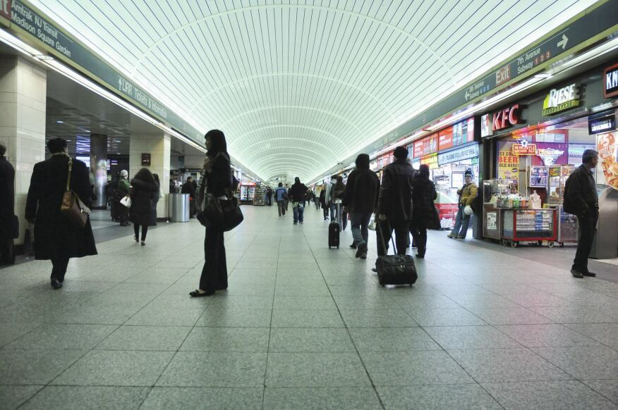 An underground passageway in the current Penn Station, with rows of shops near gates for the Long Island Railroad.