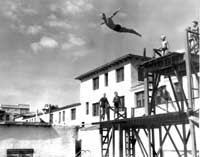 A high diver makes a giant, albeit graceful, leap into the pool. Below, a group of swimmers gets set during a 1942 swim meet.