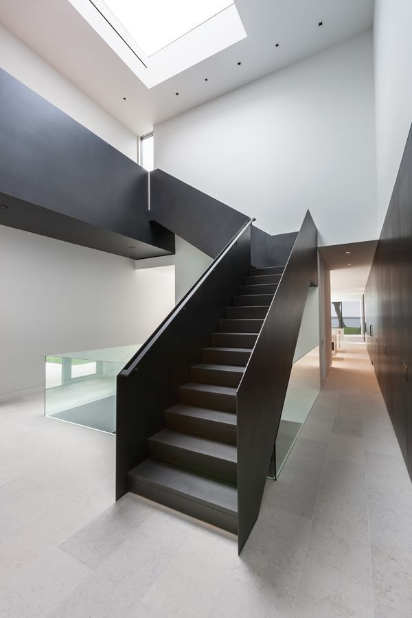 A custom steel stair marks the main entry and the connection point between the house's two volumes. The double-height space culminates in a custom skylight from Empirehouse.