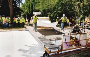 The contractor fabricated an efficient moving platform to place a wet-curing membrane over the freshly placed pavement.