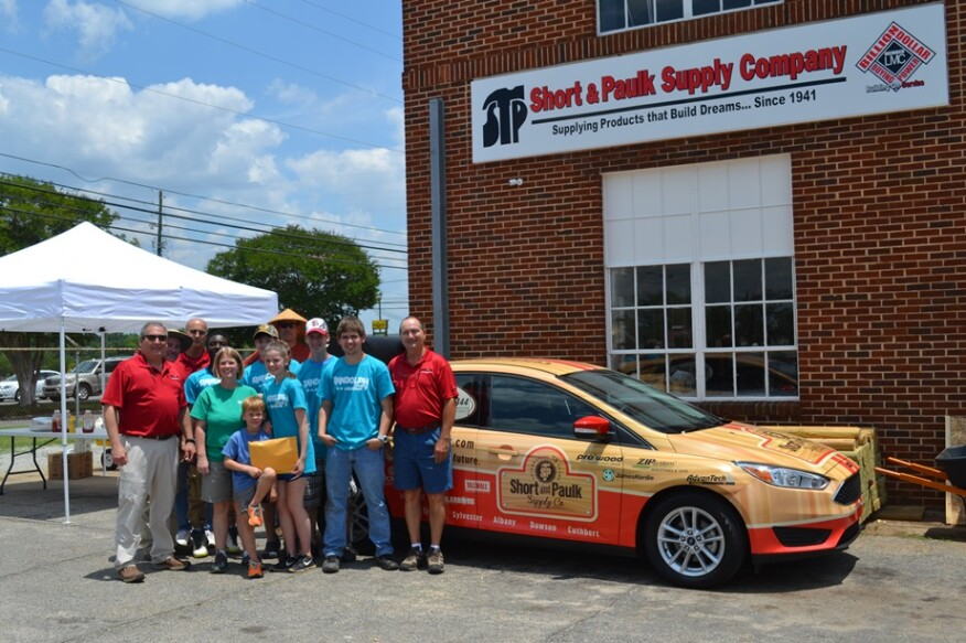 Members of the Short & Paulk team pose with the car that the dealer gave away as part of its 75th anniversary marketing campaign.