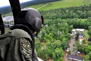 A Coast Guardsman looks out from an MH-65 Dolphin helicopter searching for stranded residents in Baton Rouge, LA on Aug. 15, 2016. Photo by Petty Officer 1st Class Melissa Leake (photo from the U.S. Department of Agriculture via Flickr).