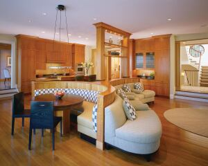 Anchoring a room that contains a kitchen, breakfast area, and family sitting area, the upholstered cherry piece turns a different face to each function: a counter with a bar sink toward the kitchen, a semicircular seating booth at the breakfast area, and a lower, compound-curved built-in sofa facing the family rooms fireplace.
