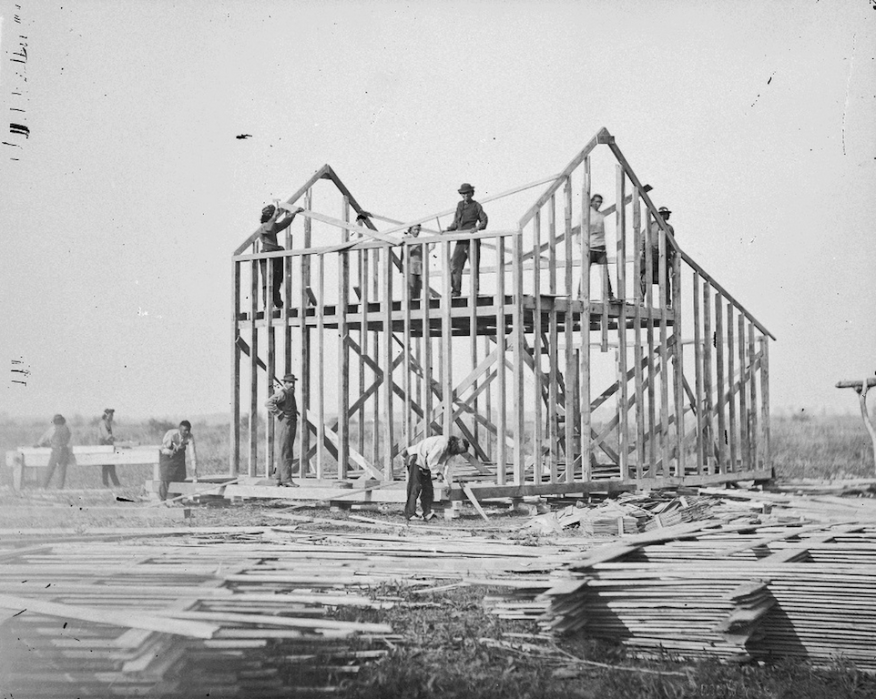 Figure 1: Ten men building a wood frame house on a Omaha Reservation in Nebraska in 1877  (Photo by William Henry Jackson: The National Archives, Smithsonian Institution) Source: National Endowment for the Humanities, http://www.neh.gov/files/divisions/public/images/05_balloon-framing_resized.jpg