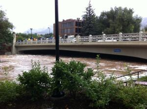 Boulder Creek rising under a bridge in downtown Boulder. Deep beneath the flood waters are multiple lanes of bike and walking paths and a tall scenic waterfall.