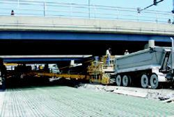 Clearances under the 20 overpasses limited dump truck access, so Walsh used the 35-foot conveyor on the trimmer to move concrete to where it was needed.
