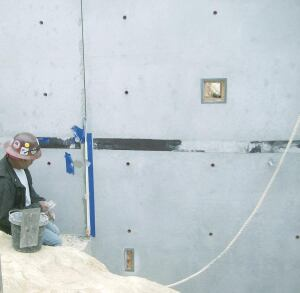 Using a small pointed mason trowel, the cement finisher applies the color matched patching material.