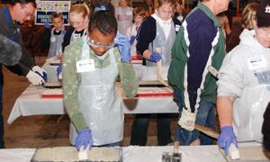 Each day, 60 school kids learned about bridge construction and the properties of concrete. Shown here, a student strikes off her tile.