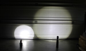 "The narrow beam and shadows on the left are typical of flashlight-style work lights. The large shadow-less beam on the right is from the WorkStar 2000. Both lights are 24"" away from the inside of a garage door."
