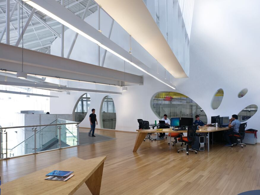 Oval windows in the research offices, which are outfitted with desks designed by Brooks + Scarpa, overlook the manufacturing lab high-bay space next door, allowing visual connections between the teams.