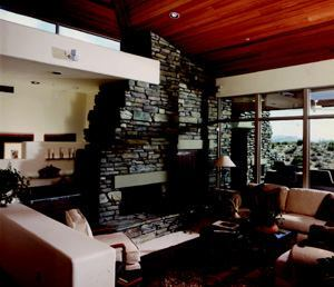 MIRROR IMAGE: A native stone fireplace (left) looks at home inside or out, extending on either side of a glass wall and picking up the same sandstone lintel details throughout. The treatment earned a 1996 special focus award for this Scottsdale, Ariz., house.