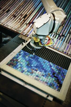 Artaic's robot, which is named Arty, picks up and assembles individual mosaic tiles into 1-square-foot grids that are derived from the tesselated image file created in the company's software. These grids of tiles are then anchored to backing to become a mosaic tile sheet. One large mosaic can comprise roughly 1,500 such sheets, which are installed on site.