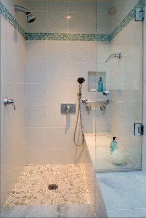 The custom shower has an 18-inch-high bench that extends from inside to outside, and glass doors (installed after this photo was taken) that swing both in and out to make it easier for the homeowner to maneuver.With accessible showers, Dan Tibma says, it's good to have two showerheads, one fixed and one that slides on a bar that the user can reach and adjust as needed. Instead of installing 36- and 48-inch grab bars at an angle, with the high end at the shower as suggested in some manuals, Tibma installs the bar horizontally level so the room doesn't look institutional and the grab bar can function as a towel holder. Niches are great for keeping soap and shampoo tucked out of the way, he says.
