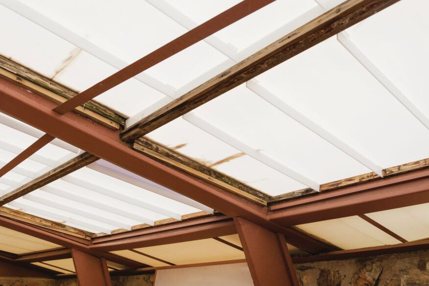 Sagging acrylic roof panels are leading to water infiltration and deteriorated blocking.