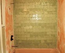 A mottled bond coat pattern may become visible through translucent or transparent glass tiles when they are installed over a waterproofing membrane.