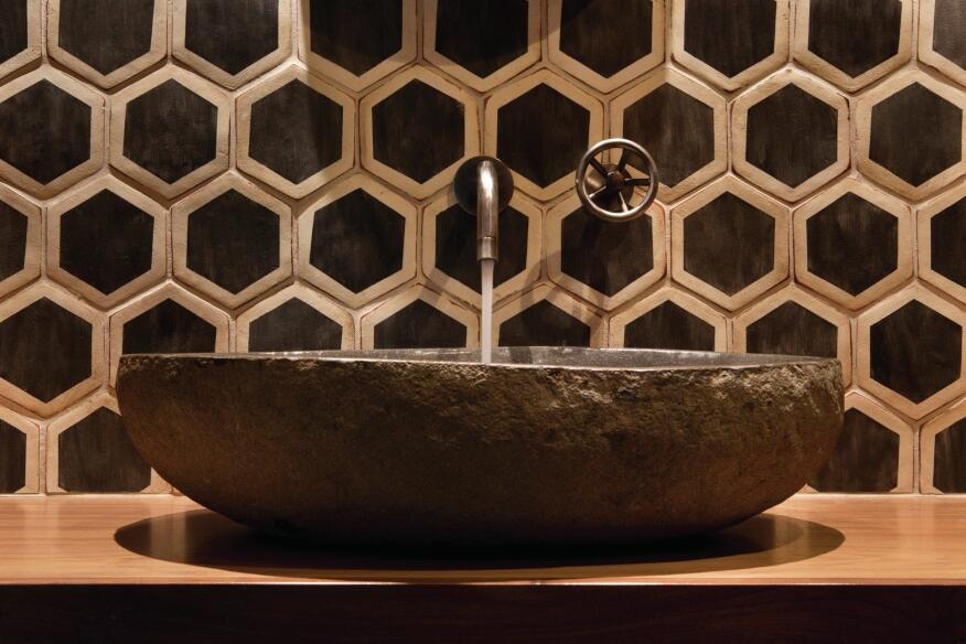 Bold wall tile, a stone sink, and a simple wall-mounted fixture might not work in a bigger or busier bath, but here, they pack a visual punch.