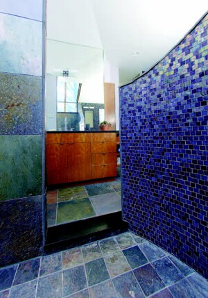 One interior shower wall is covered with a combination of iridescent and matte glass tile. His vanity area, opposite the shower, includes a mirrored wall that adds to the feeling of spaciousness in the bath and reflects the tree line outside the window-skylight.