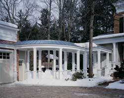 An 8-inch diameter maple tree in the path of the future walkway necessitated that the walkway first form a pavilion off the porch, step right of the tree, then turn to meet the garage. As it joins the garage, the walkway's columns, built with pedestals, are repeated.