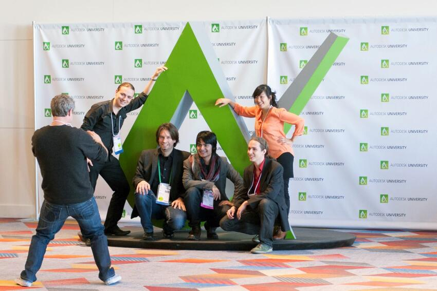 Attendees posed next to the Autodesk University logo sculpture.