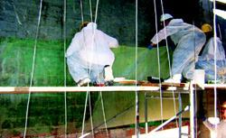 Workers are applying FRP to strengthen a hollow-clay tile wall.